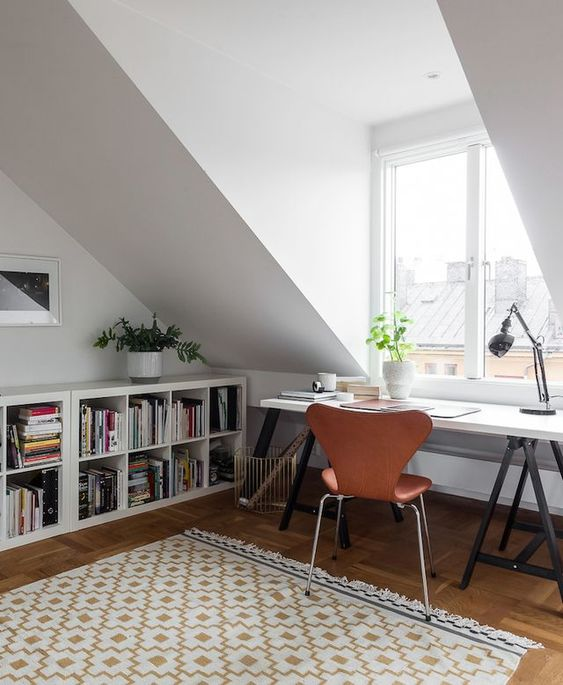 a welcoming attic home office with open bookshelves, a trestle desk, an amber leather chair and a vintage table lamp is cool