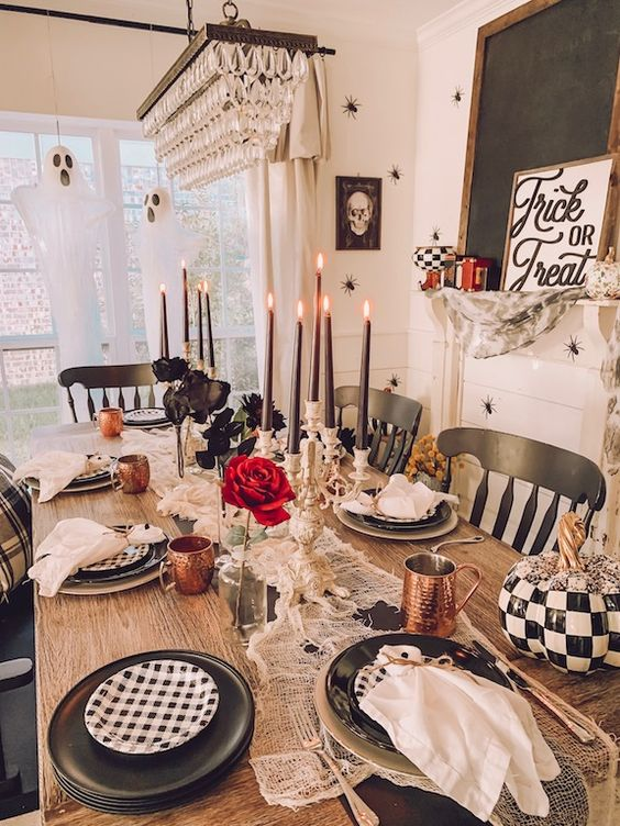 a whimsy Halloween tablescape with black and white plates, copper mugs, red and deep purple blooms, black candles