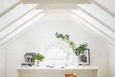 a white attic home office with wooden beams on the ceiling, a white desk, a stained chair, a small arched window is welcoming