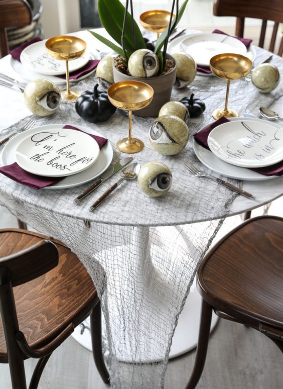 a wicked Halloween tablescape with cheesecloth, black pumpkins, white plates, purple napkins and large eyeballs