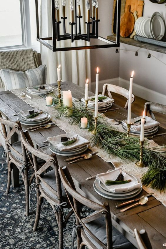 a winter table setting with an evergreen table runner, various candles, bells, neutral porcelain