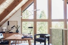 an attic home office with a wooden desk and a storage unit, black chairs, some lamps and a gorgeous view through double-height windows
