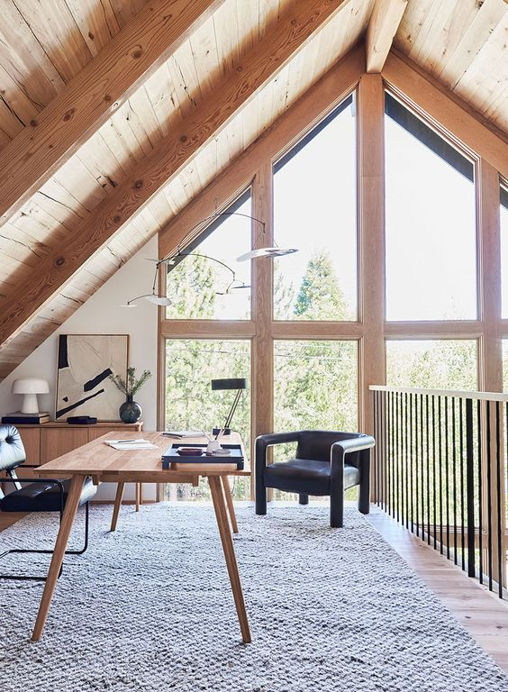 an attic home office with a wooden desk and a storage unit, black chairs, some lamps and a gorgeous view through double height windows