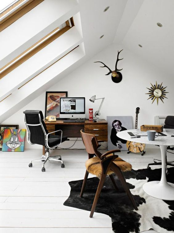 an eclectic attic home office with large skylights, a stained desk and a black leather chair, a round table and a wooden chair, a cool rug and some artworks