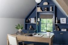 an elegant farmhouse attic home office with a blue accent wall with built-in storage, a stained desk and a neutral chair, pendant lamps