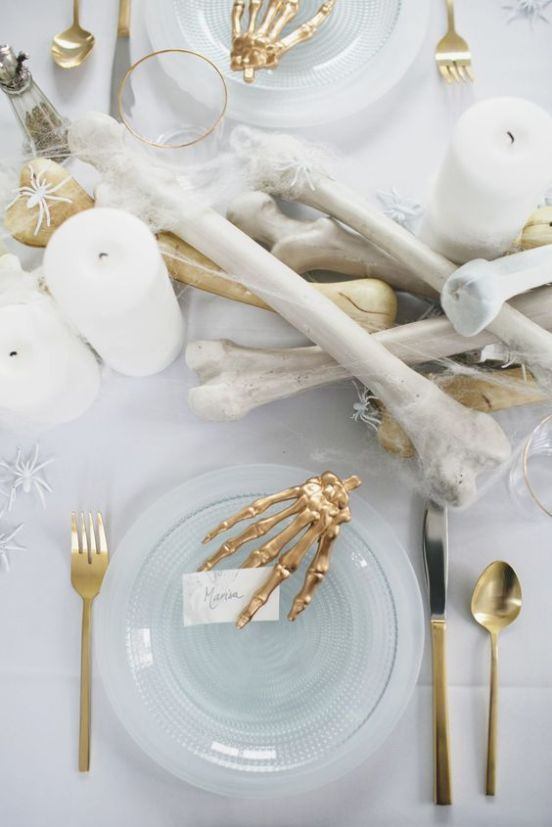 an elegant white and gold Halloween tablescape with bones, white spiders, candles, gold skeleton hands and glass plates