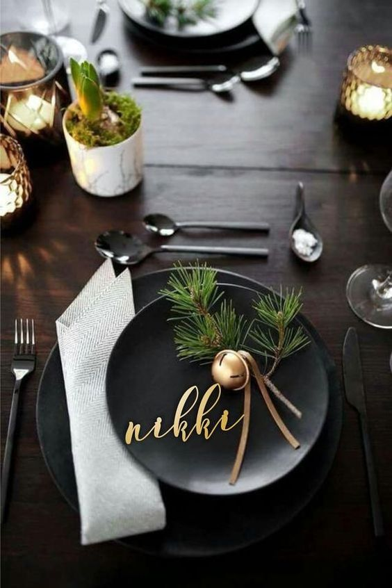 an elegant winter tablescape with black plates, bells with evergreens, bulbs in pots and candles