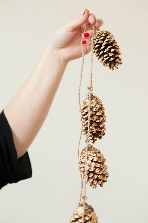 Gold glitter spray paint is a good way to make your pinecone garland shiny.