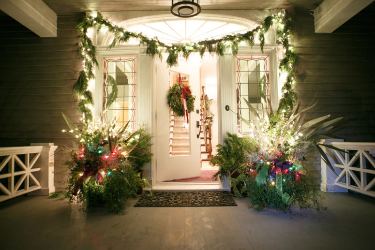 Disguise unsightly wires from string lights by winding them around a column or post with Christmas greenery.