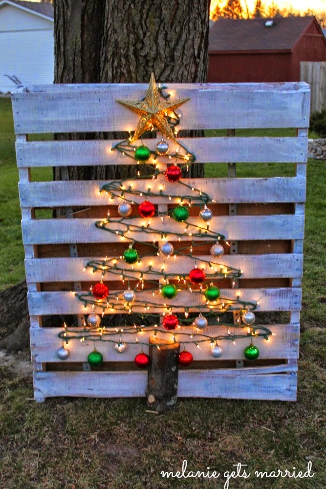 This DIY Christmas tree is made by putting nails on a pallet and stringing lights and ornaments along them.