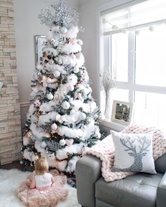 a Christmas tree decorated with white and silver ornaments, lights and fluffy fur garlands plus a large silver topper