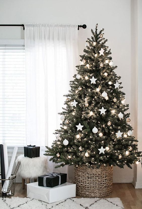 a Christmas tree with lights, balls and star ornaments and metallic ones for an elegant Scandinavian tree