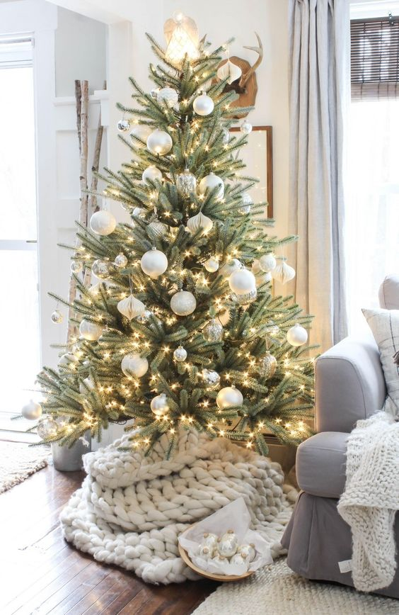 a Christmas tree with lights, silver and white ornaments plus a shiny lamp on top