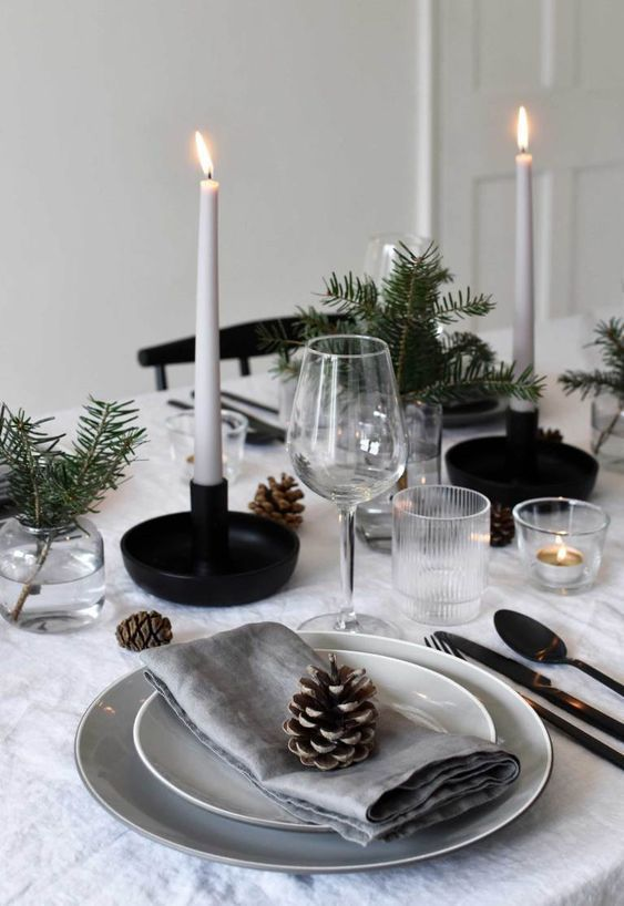 a Nordic Christmas table with neutral linens, white candles, pinecones, evergreens for a cozy Christmas dinner