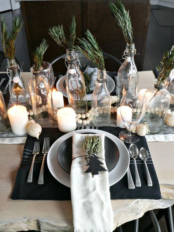 a Nordic Christmas tablescape with candles, beads, a black placemat, greenery in bottles for a natural feel