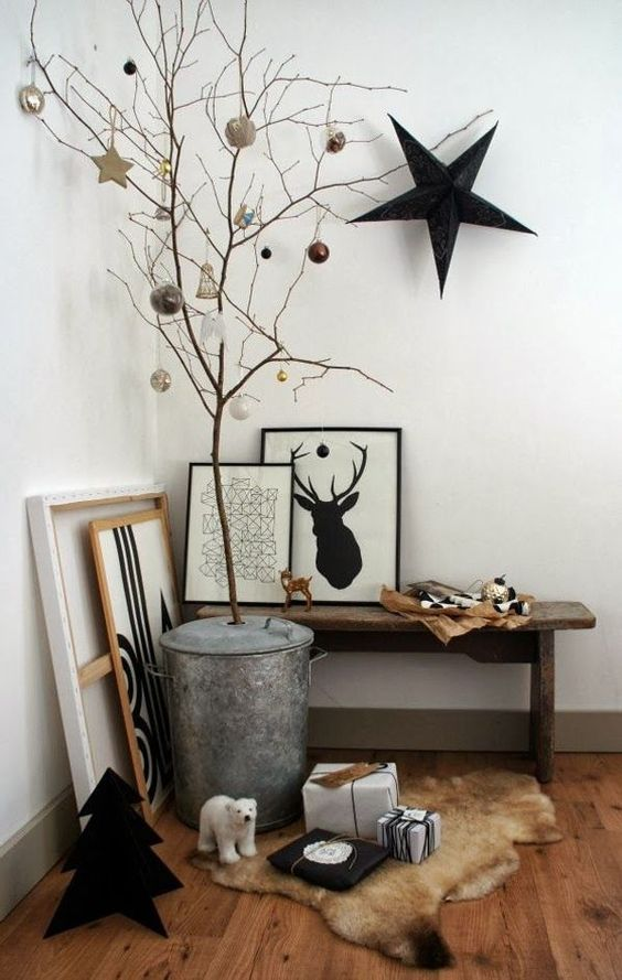 a Nordic entryway space with some artworks, branches with ornaments and a large black star on the wall