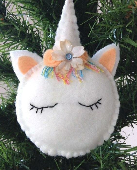 a beautiful unicorn Christmas ornament with colorful yarn, beads and a fabric bloom is amazing