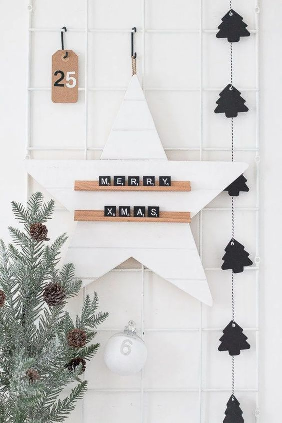 a black Christmas tree garland, a pale tree with pinecones and a star with scrabble letters