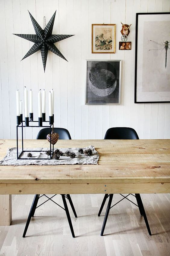 a black modenr candelabra with pinecones and a blakc star on the wall for a Nordic feel