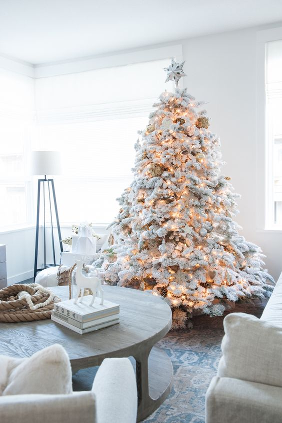 a flocked Christmas tree with matching white and silver ornaments and lights