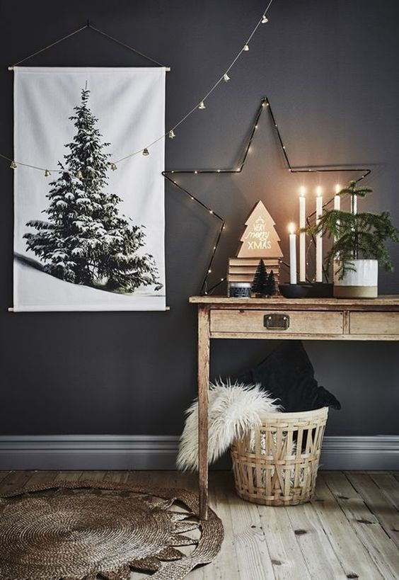 a lit up star, a Christmas tree artwork, a mini tree in a pot and a basket with pillows