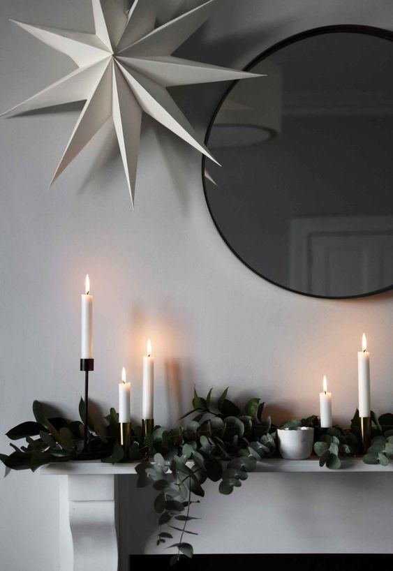 a mantel decorated with eucalyptus, white candles and a large paper star over it all for a Nordic feel