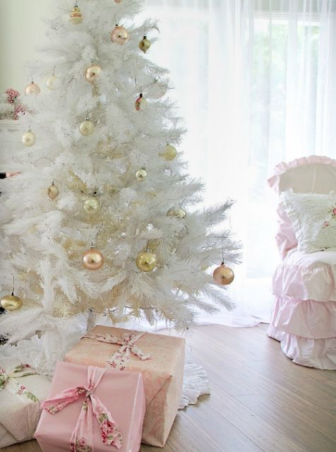a medium size white Christmas tree with gold and copper ornaments looks glam and shiny