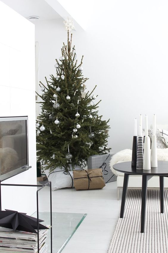 a minimalist Christmas tree with sheer and metallic ornaments and white and black candleholders