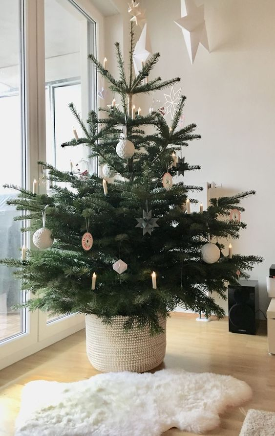 a modern Nordic Christmas tree with white ornaments and lights plus a faux fur rug by it