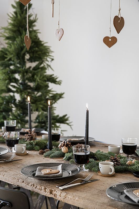 a modern Scandinavian table with evergreens, pinecones, black candles and porcelain, gingerbread cookies and simple cups