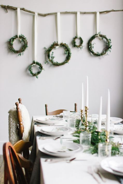 a modern and fresh Nordic table with greenery, gold candleholders, white porcelain and an arrangement of wreaths on the wall