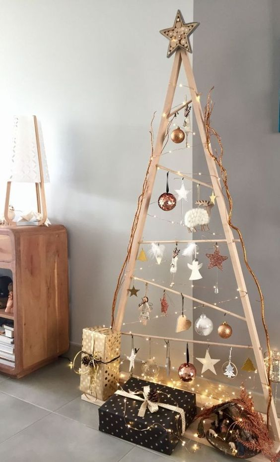 a modern framed Scandinavian Christmas tree with lights, white and copper ornaments and glam gift boxes