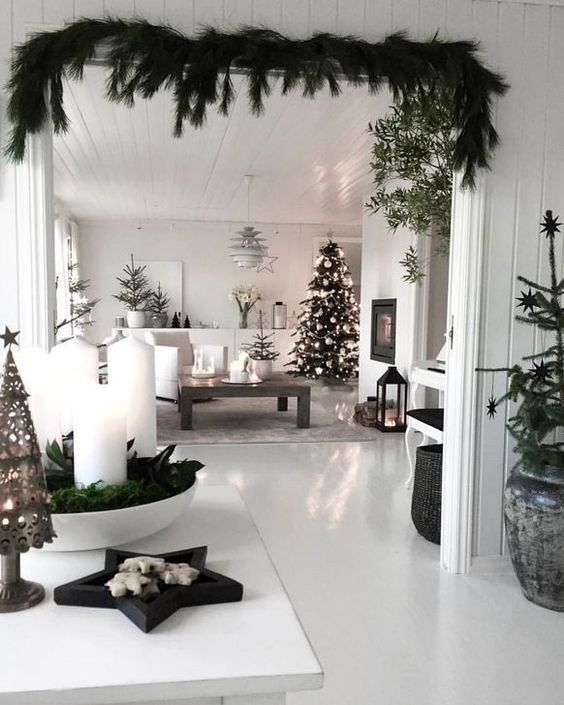a monochromatic Scandi space with evergreens, white ornaments, candles and candle lanterns looks very modern