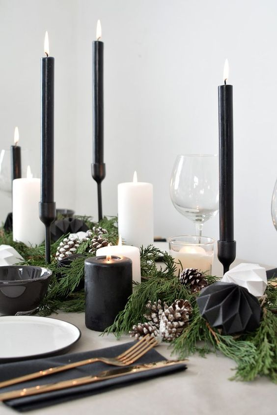 a monochromatic Scandinavian tablescape with black and white candles, evergreens, pinecones and white porcelain