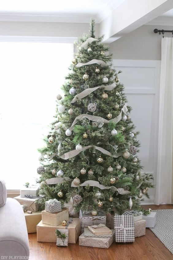 a neutral Christmas tree with lots of metallic ornaments and plaid ribbons looks very calm and cute
