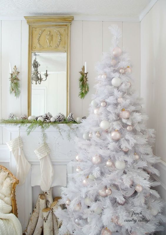 a pure white Christmas tree with tender pastel and white ornaments and bead garlands is a chic idea
