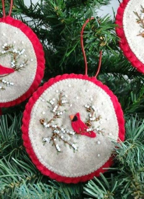 a red and white round Christmas ornament with beads and a bird applique is a bold and chic idea to rock