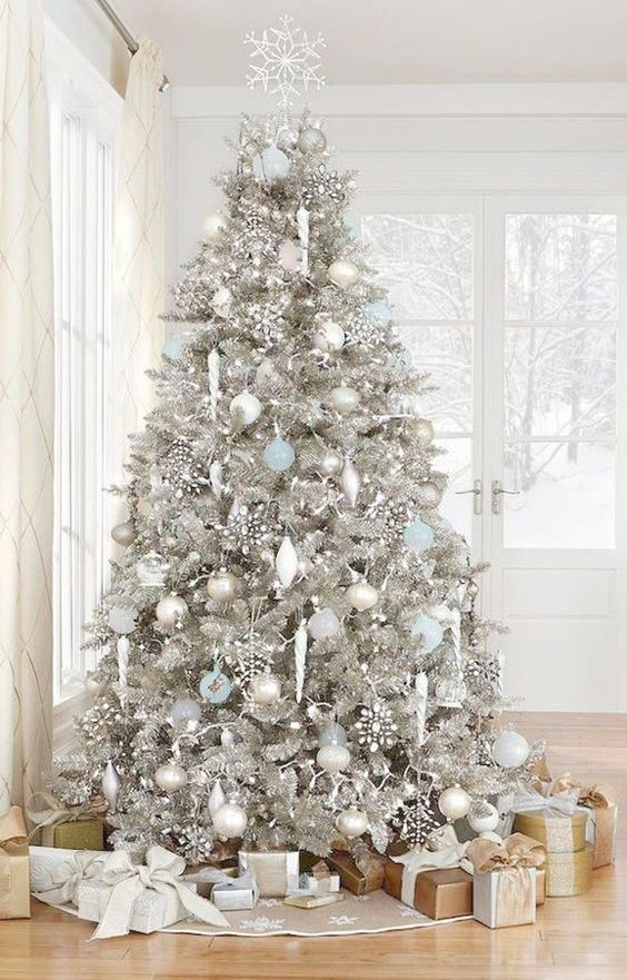 a silver Christmas tree with white, silver and blue ornaments, rhinestone snowlakes and some lights