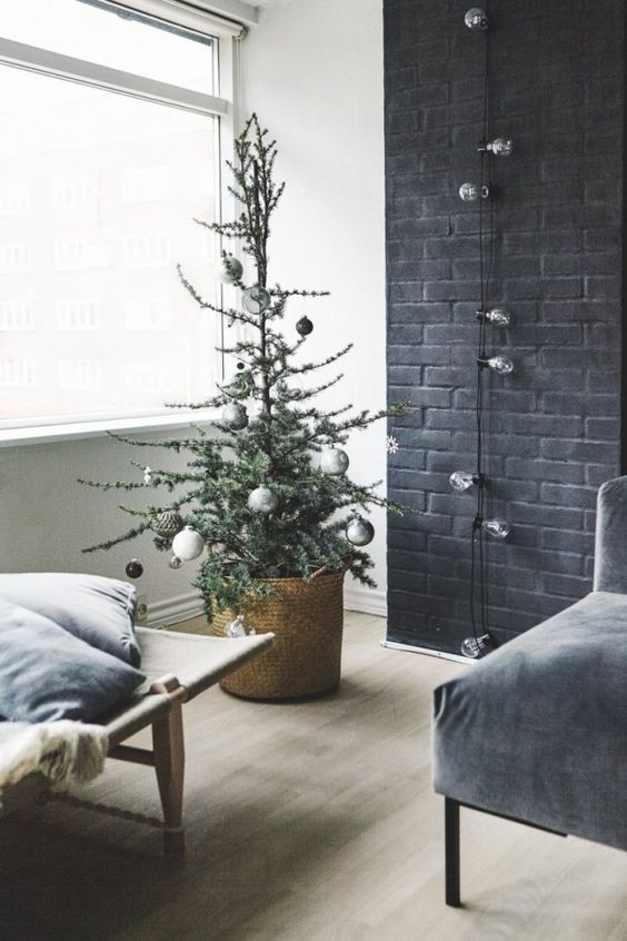 a small Christmas tree with metallic and black ornaments in a basket for a Nordic feel