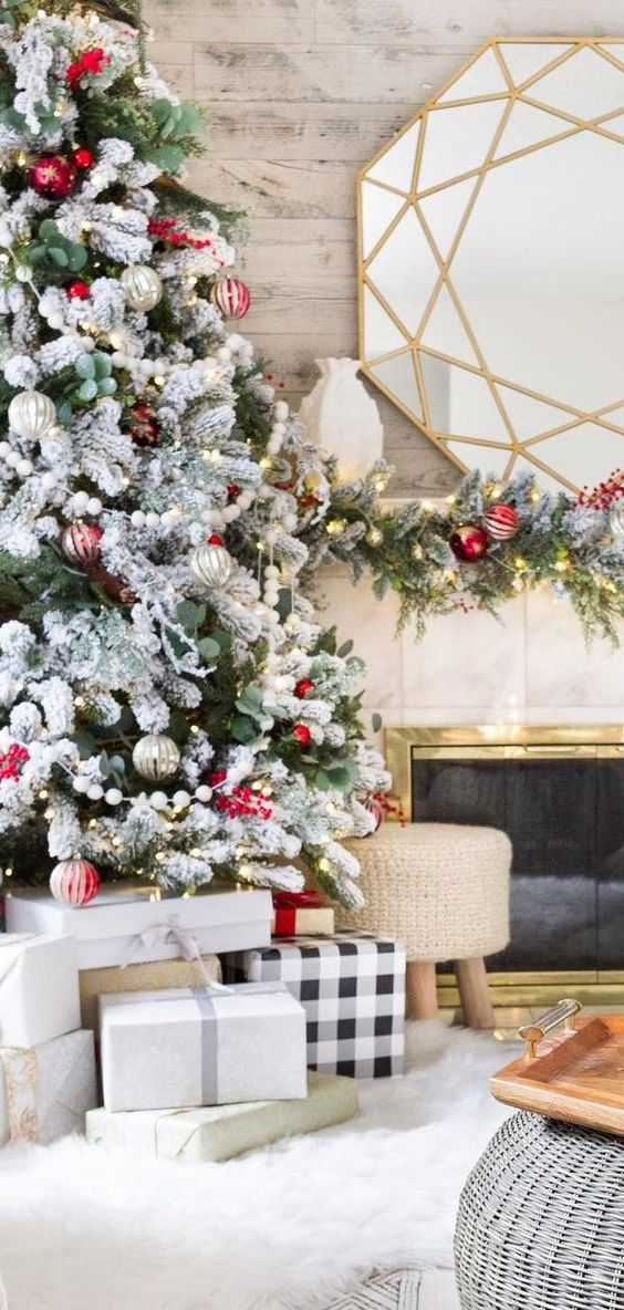 a snowy Christmas tree decorated with red and silver ornaments and fresh greenery for a bold festive look