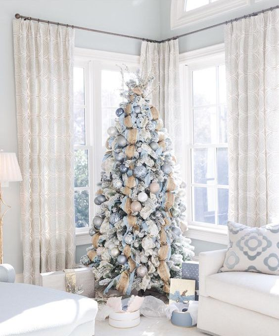 a snowy Christmas tree with blue, silver and tan ornaments plus burlap ribbons and a large branch topper