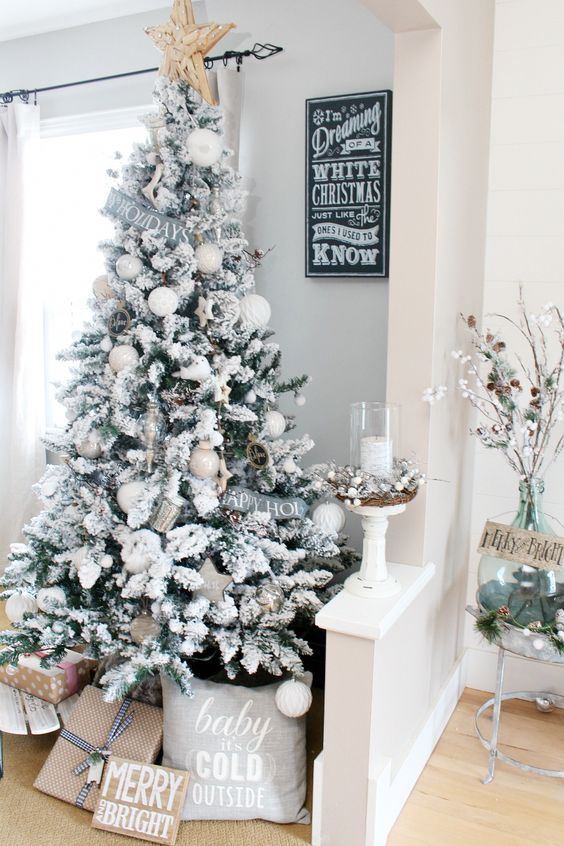 a snowy Christmas tree with metallic and white ornaments, stars, signs, a large star on top