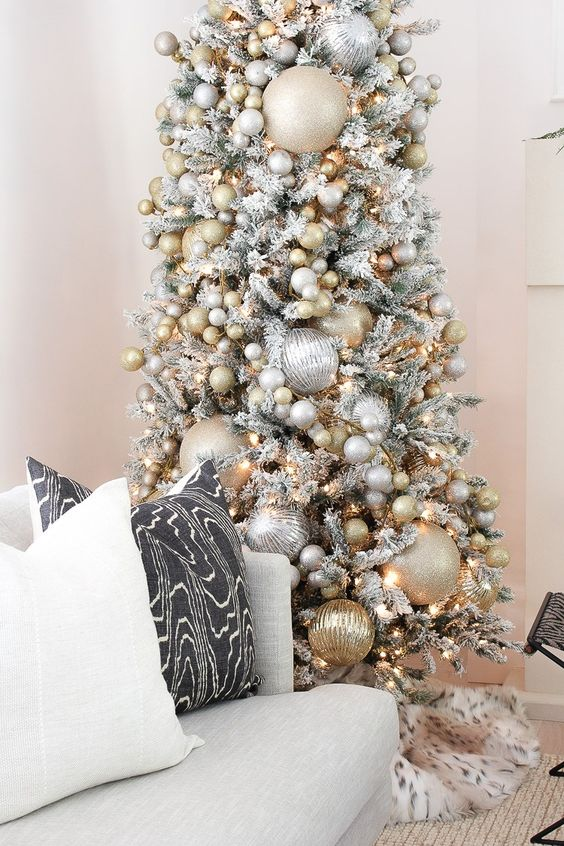 a snowy Christmas tree with oversized and smaller metallic Christmas ornaments plus lights