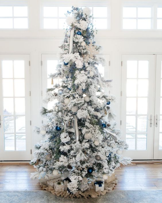 a snowy Christmas tree with white and bold blue ornaments and striped ribbons plus a burlap skirt