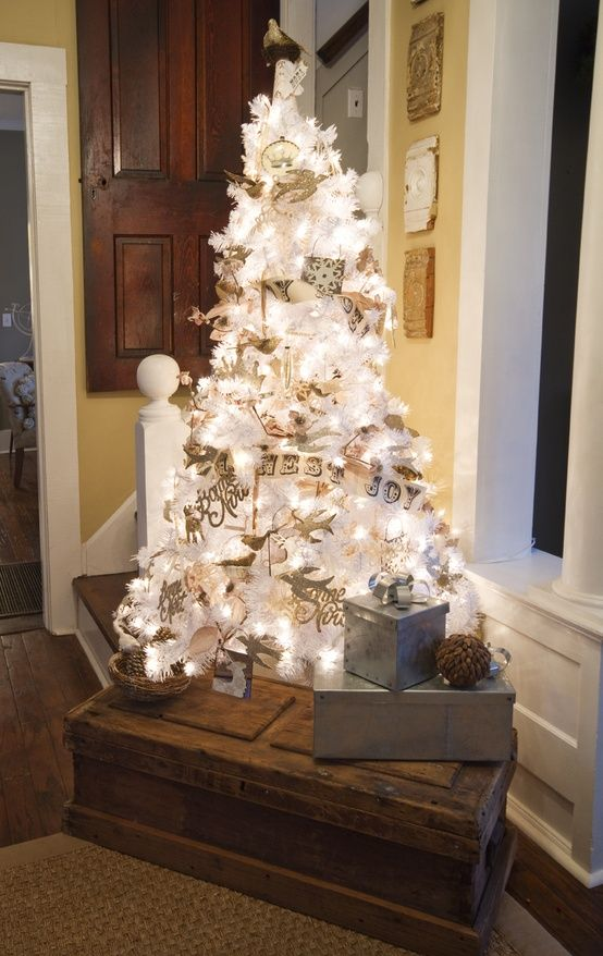 a white Christmas tree with lights decorated with vintage-inspired ornaments and paper buntings is very cool