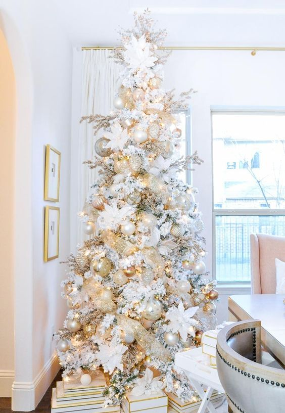 a white Christmas tree with white, mother of pearl and metallic ornaments, lights and fabric blooms in white