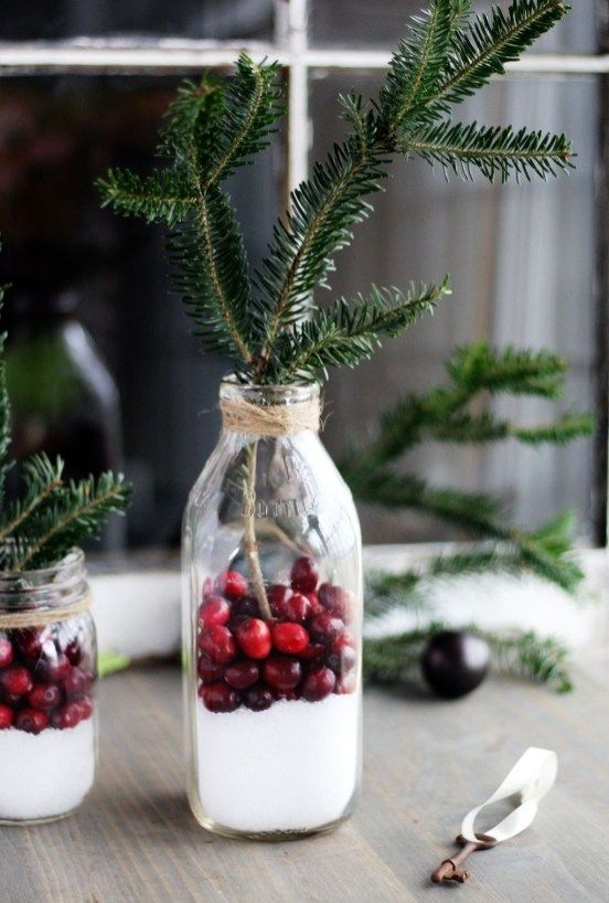 bottles with evergreens, cranberries and faux snow can be used as Scandinavian centerpieces
