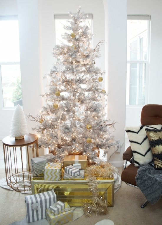 metallic decor ideas - a silver tree with gold and white ornaments and gift boxes wrapped with gold and silver