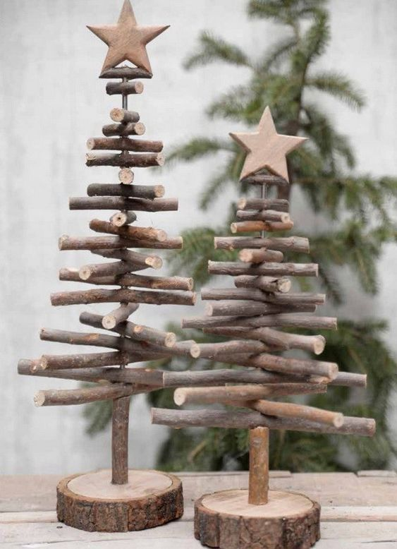 Christmas trees made of sticks with wooden stars placed on wooden slices for a rustic touch