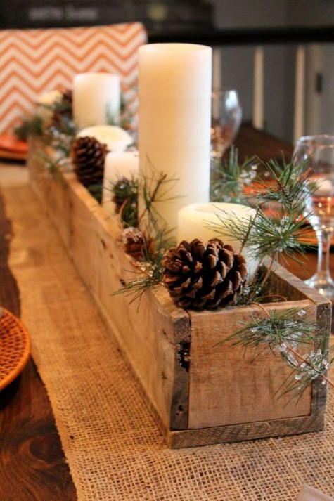 a Christmas centerpiece of a wooden box, evergreens, pinecones and pillar candles is very cozy